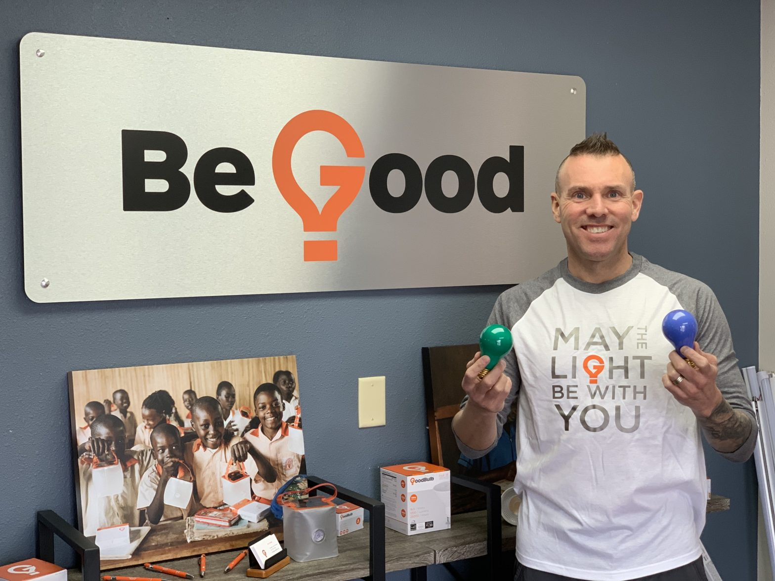 """Tom Enright poses with a blue and green lightbulb, with a sign reading """"Be Good"""" behind him."""