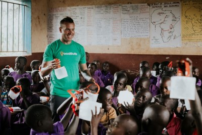 Tom Enright holds up a solar LED lantern in a classroom in Uganda, surrounded by children.